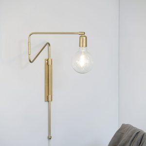 Swing fra House Doctor er en smuk væglampe med et innovativt og smukt look i messing. Væglampens lette form er skabt med asymmetriske og skæve linjer Det giver væglampen et dekorativt og spændende look. Lampen er lavet af messingbelagt jern. Messingfinishen tilfører både varme og personlighed til din boligs indretning. Messing er flot til en enkel og nordiske stil men er også smuk i kombination med klassiske retromøbler. Hæng lampen ved siden af sengen som en smuk sengelampe eller brug en som lyskilde ved sofaen eller en stol i stuen. Pære medfølger ikke. Mål: l: 70 cm. E14